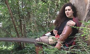 Curly-haired bitch in high boots masturbates outdoors